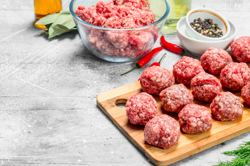 Raw beef meatballs with spices and fragrant dill .